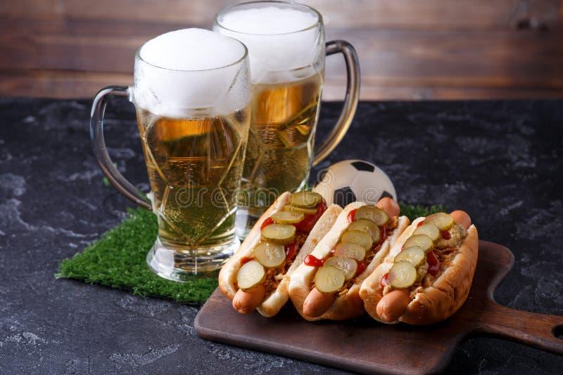 Fotografia dwa szkła piwo, hot dog, piłki nożnej piłka obrazy royalty free