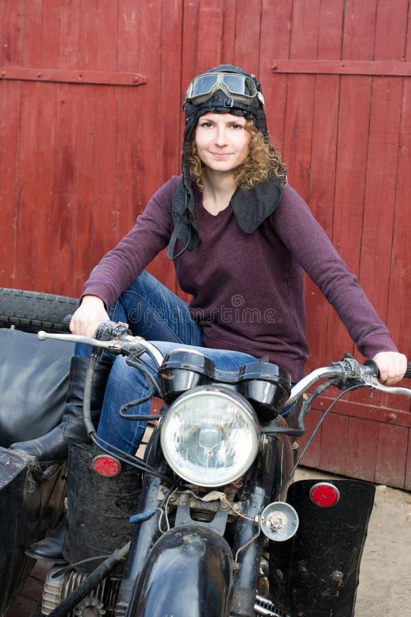 Fotografia dziewczyna na rocznika motocyklu w pilotowej nakrętce zdjęcia royalty free