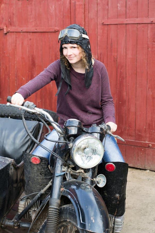 Fotografia dziewczyna na rocznika motocyklu w pilotowej nakrętce obraz royalty free
