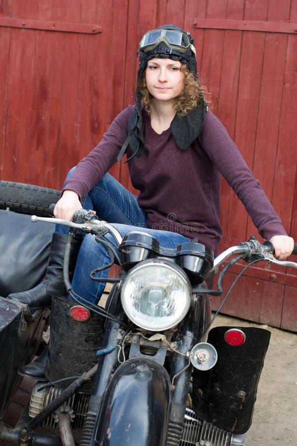 Fotografia dziewczyna na rocznika motocyklu w pilotowej nakrętce fotografia royalty free