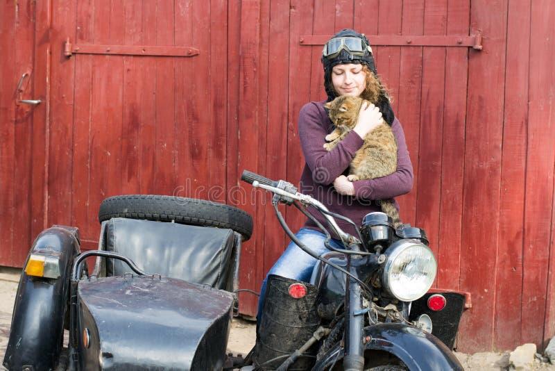 Fotografia dziewczyna na rocznika motocyklu w pilotowej nakrętce z kotem zdjęcia stock