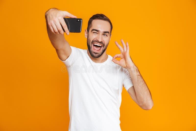 Fotografia emocjonalny facet 30s w przypadkowej odzieży śmia się selfie na telefonie komórkowym i bierze, odizolowywająca nad żół zdjęcie royalty free