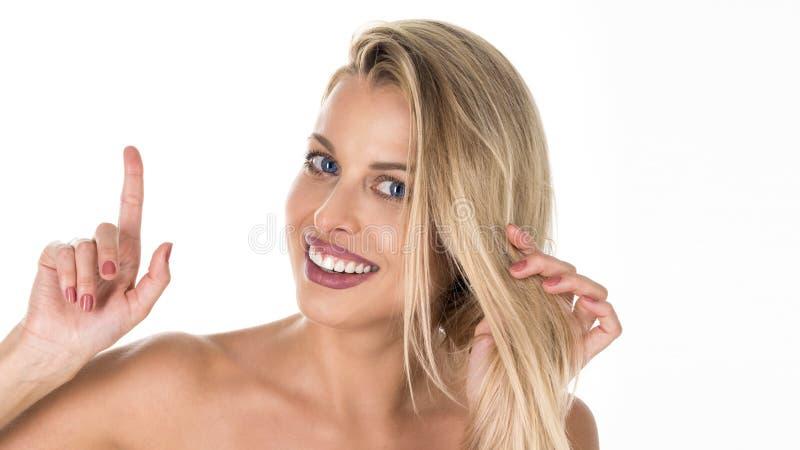 Fotografia energiczna ładna uśmiechnięta dama jest ubranym popielaty odgórny odosobnionego na białym tle wskazuje jej palec w Eur obraz royalty free