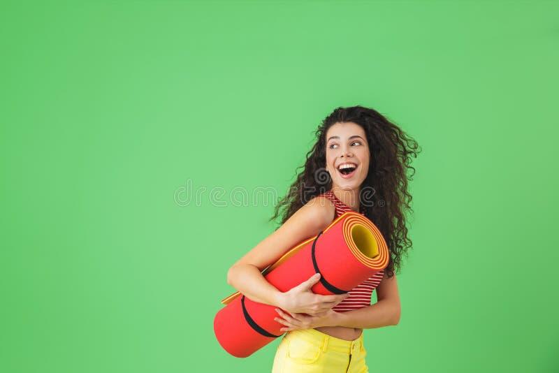 Fotografia europejska kobieta 20s u?miecha si? joga mat? i niesie podczas treningu obrazy royalty free