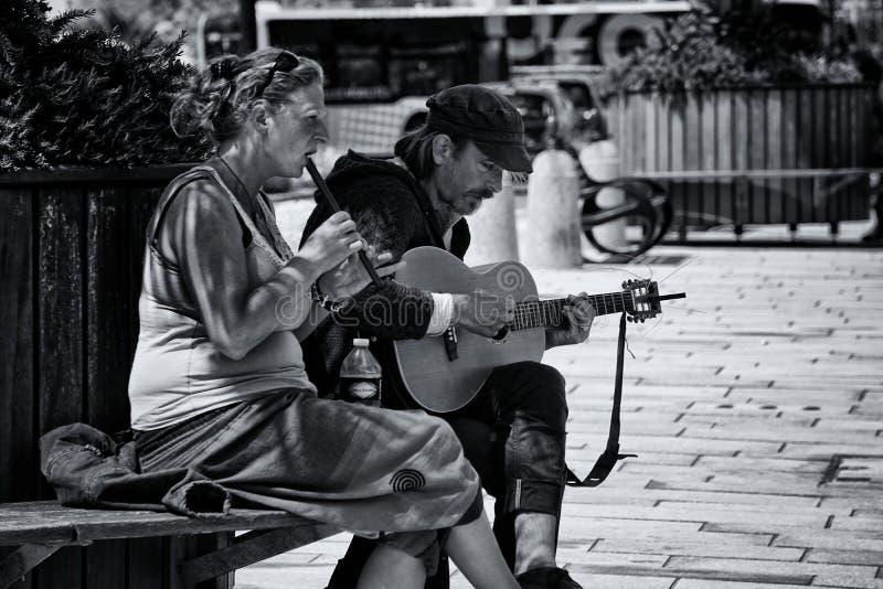 Fotografia Greyscale do homem e da mulher que jogam instrumentos musicais imagem de stock