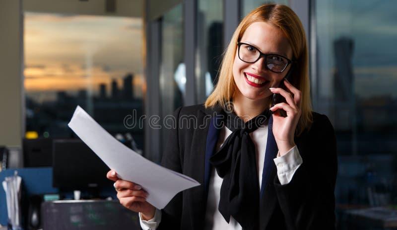 Fotografia jest ubranym szkła opowiada na telefonie uśmiechnięta kobieta zdjęcie royalty free