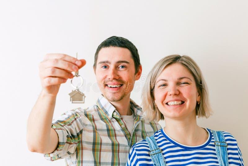Fotografia kobieta i mężczyzna z kluczami od mieszkania przeciw pustej ścianie zdjęcie royalty free
