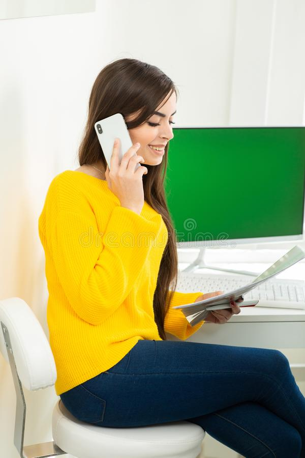 Fotografia kobieta, opowiadaj?cy na telefonu i czytania dokumentach w biurze Zielony ekran w tle zdjęcie royalty free