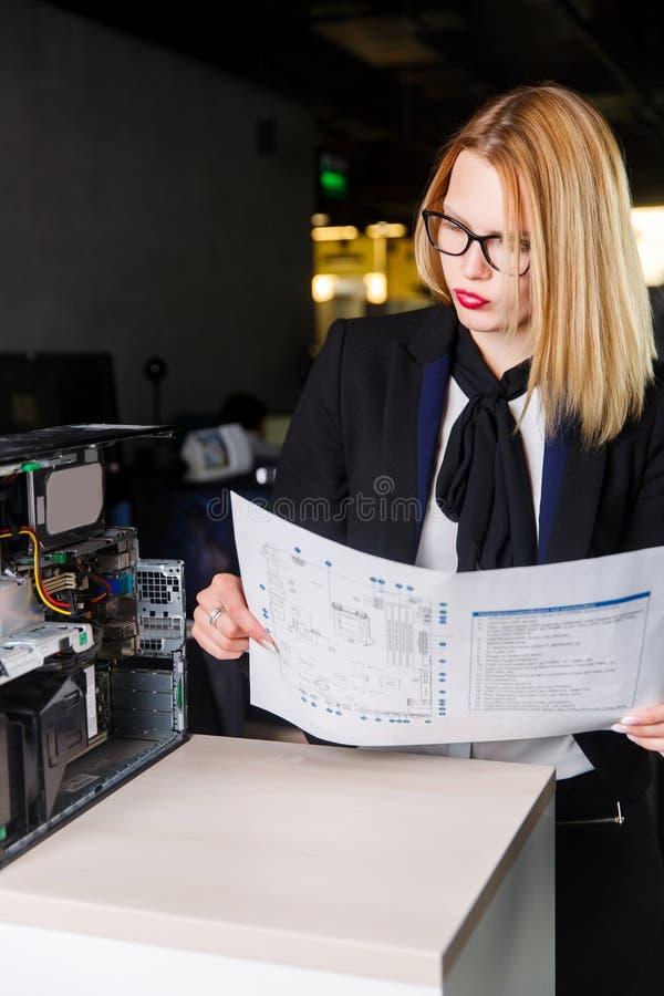 Fotografia kobieta w szkłach z diagramem w rękach obok łamanego procesoru fotografia royalty free
