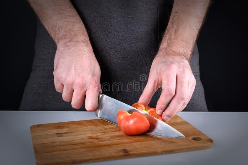 Fotografia kulinarny proces Mężczyzna ciie pomidoru z ostrym nożem Obrazek z winietą obraz stock