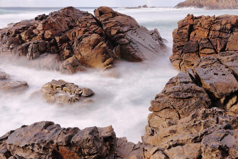 FOTOGRAFIA LUNGA DI ESPOSIZIONE SULLE SCOGLIERE DELLA ROCCIA SULLA COSTA DELL'OCEANO ATLANTICO immagini stock