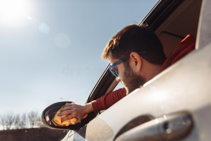 Fotografia mężczyzna myje przyglądającego samochodowego lustro przy dniem z pomarańcze łachmanem fotografia stock