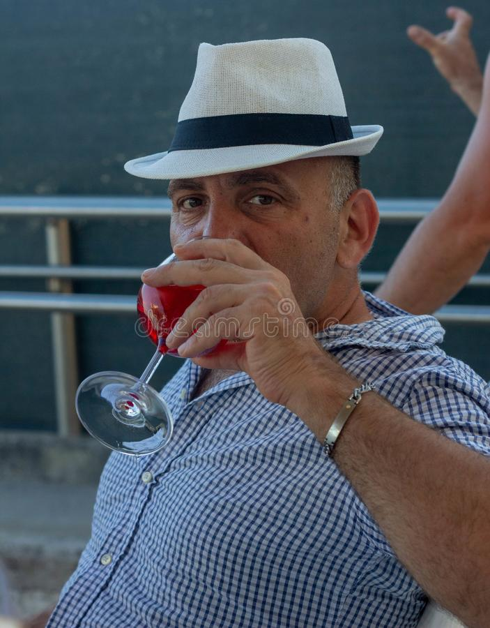 Fotografia mężczyzna pije aperitif z kapeluszem zdjęcia stock