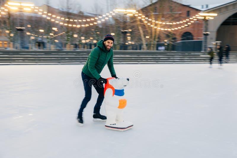 Fotografia męscy łyżwiarek utrzymania balansuje na łyżwa pierścionku, stojaki na skat fotografia royalty free