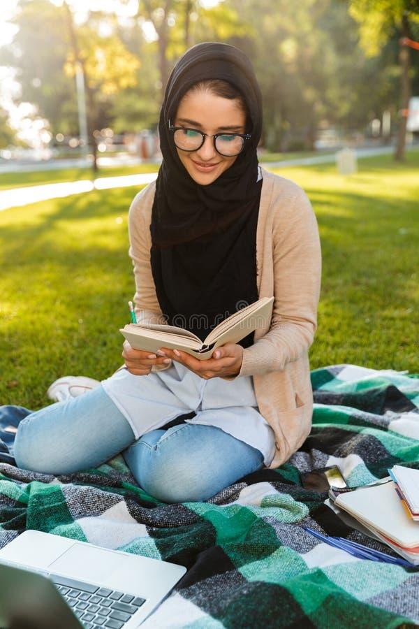 Fotografia młoda arabska kobieta jest ubranym chustki na głowę obsiadanie na koc w zieleń parku obraz stock