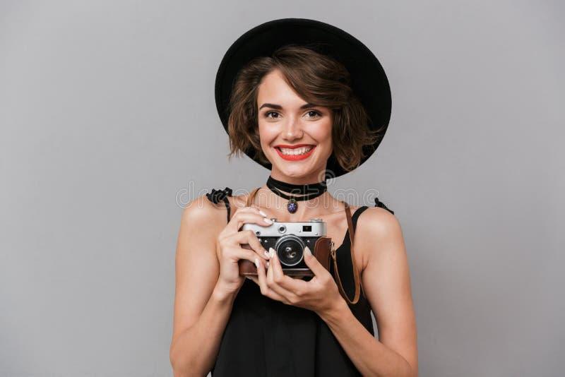 Fotografia młoda kobieta 20s jest ubranym czerni smokingowego i kapeluszowego photographi zdjęcie stock