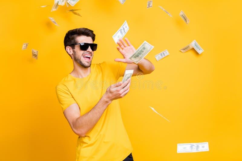 Fotografia młodego, nieostrożnego faceta wyrzucającego banknoty z domu bogacza nosi okulary przeciwsłoneczne w osobnych koszulkac obrazy royalty free