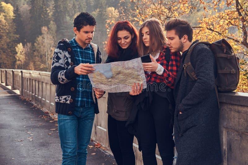 Fotografia młodzi przyjaciele patrzeje mapę i planowanie my potykamy się przy jesień lasem zdjęcia stock