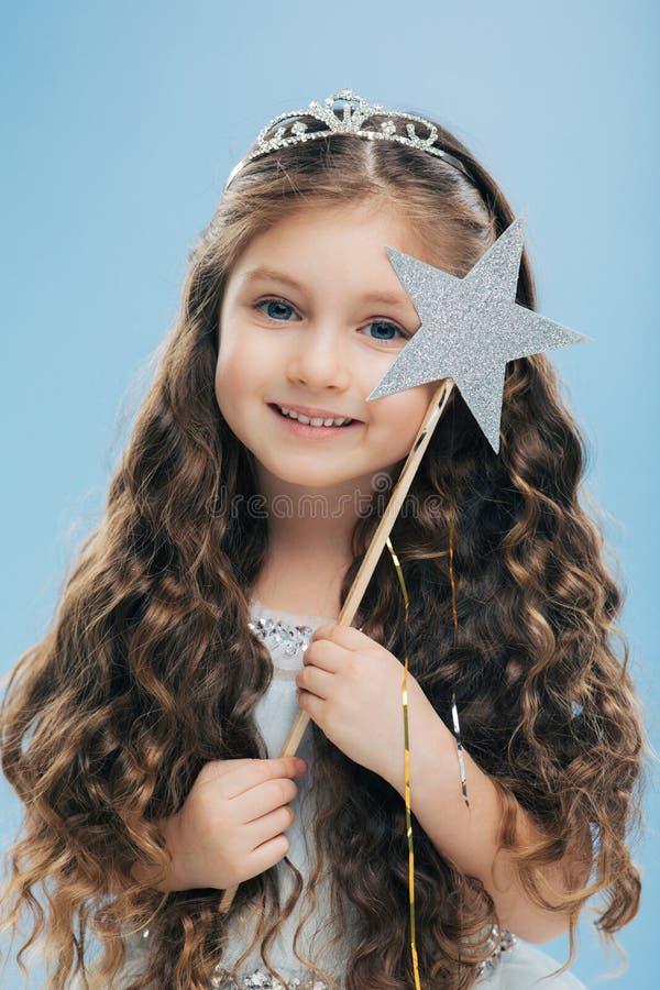 Fotografia mała czarodziejska dziewczyna z kędzierzawym ciemnym włosy, jest ubranym koronę i suknia, niebieskie oczy, delikatny u fotografia stock