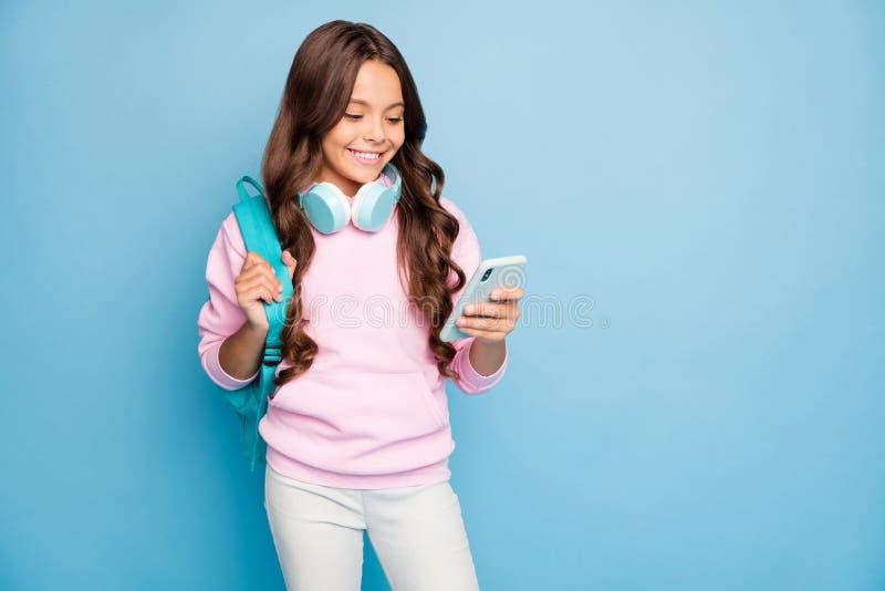 Fotografia małej szkolnej pani trzyma telefon włączający popularne piosenki młodzieżowe bezprzewodowe słuchawki noszą bluzki z lu obraz stock