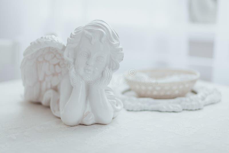 Fotografia macro da estatueta branca da porcelana do anjo que encontra-se na tabela fotos de stock