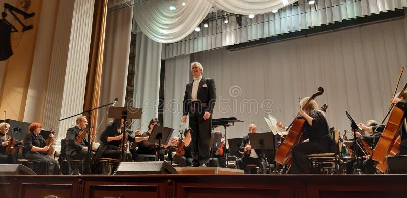 Fotografia muzycy i dyrektor Musicalu koncert w Filharmonicznym Skrzypcowy gracz Muzyki koncertowy t?o zdjęcie royalty free