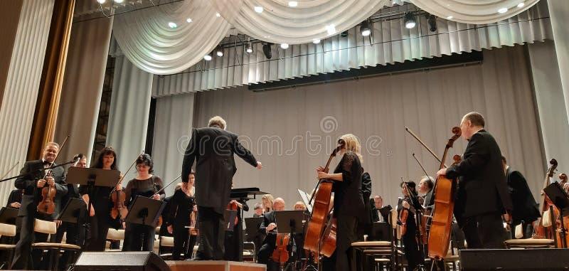 Fotografia muzycy i dyrygent Musicalu koncert w Filharmonicznym Skrzypcowy gracz Muzyki koncertowy t?o fotografia stock