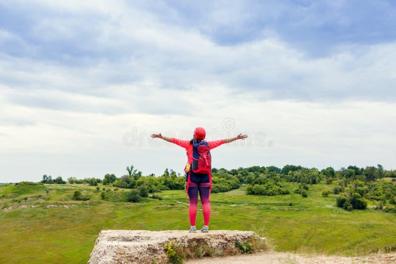 Fotografia od plecy żeński turysta z rękami podnosić na wzgórzu zdjęcie stock