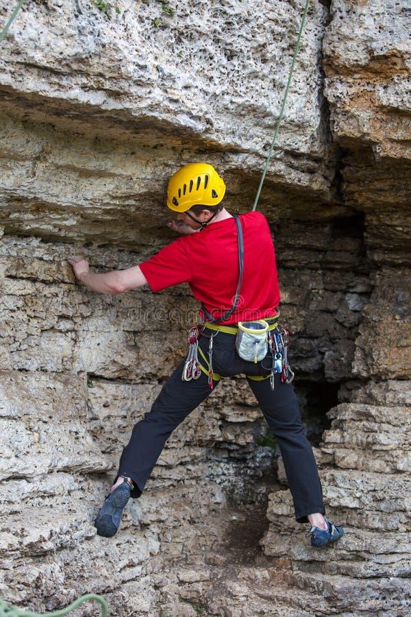 Fotografia od plecy pięcie bawi się faceta w żółtym hełmie na skale zdjęcie royalty free
