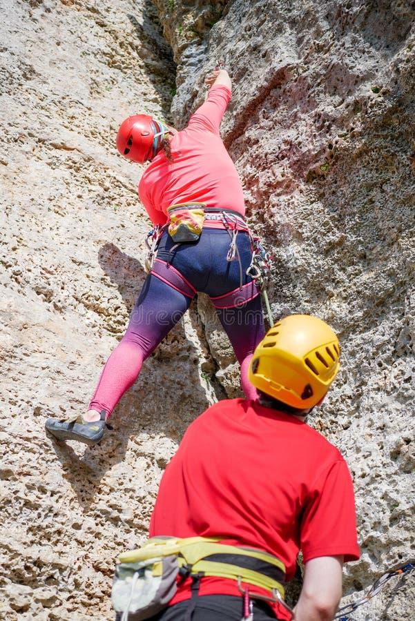 Fotografia od plecy sporty kobieta w czerwonej ciężkiego kapeluszu i mężczyzna wspinaczkowej górze up obrazy royalty free