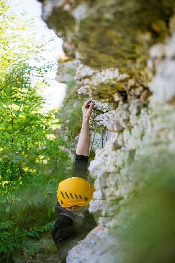 Fotografia pięcie sportów mężczyzna w żółtym hełmie na górze z zielonymi drzewami fotografia stock