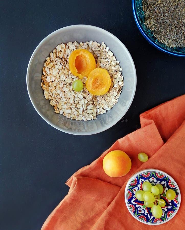 Fotografia, plakat o zdrowym łasowaniu, śniadanie oatmeal w pucharze, brzoskwinie, morele, winogrona na ciemnym tle zdjęcia stock