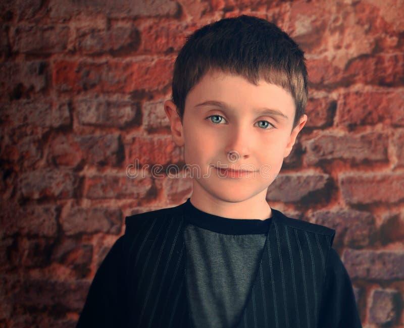 Fotografia portret Młoda chłopiec z ściana z cegieł obrazy stock
