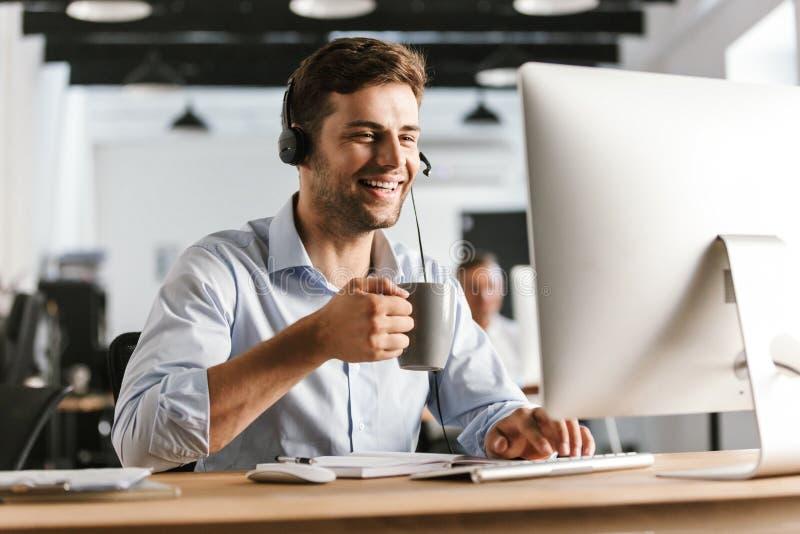 Fotografia pracownika mężczyzna 20s jest ubranym biuro odzieżowego i hełmofony, zdjęcie royalty free