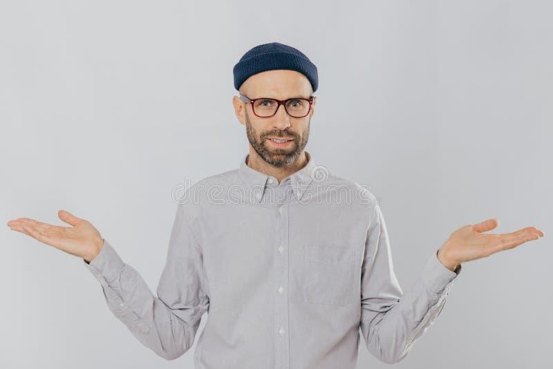 Fotografia przystojny mężczyzna z niepewnym wyrażeniem, rozprzestrzenia ręki, jest ubranym, szkła i kłobuk odizolowywających nad  fotografia royalty free