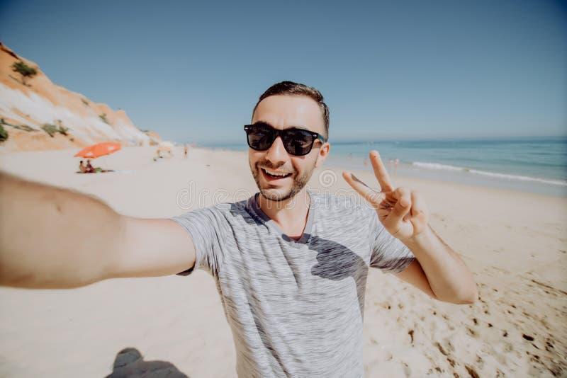 Fotografia przystojny szczęśliwy młody człowiek w okularach przeciwsłonecznych robi selfie kamerą na plażowym pokazuje pokoju ges zdjęcie royalty free
