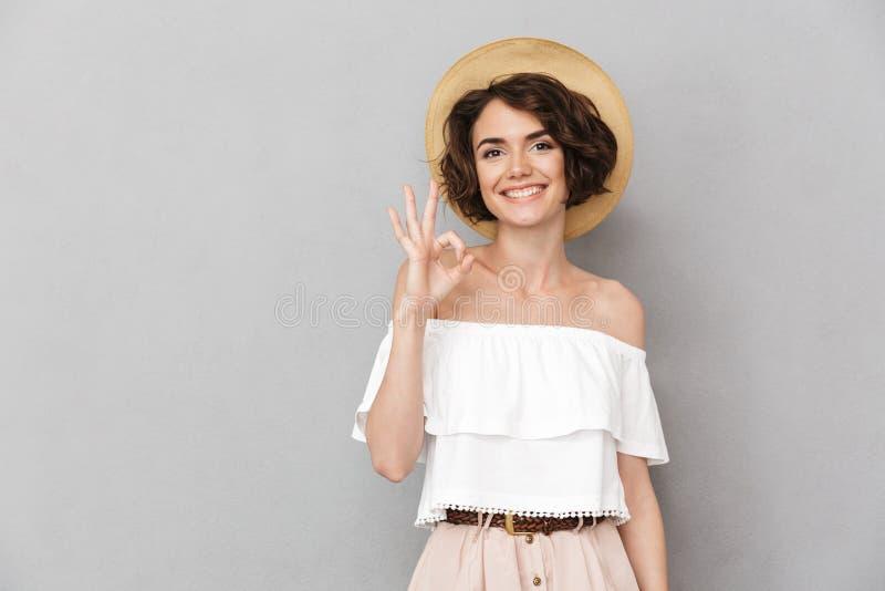Fotografia radosna brunetki kobieta 20s jest ubranym słomianego kapelusz i lato zdjęcia stock