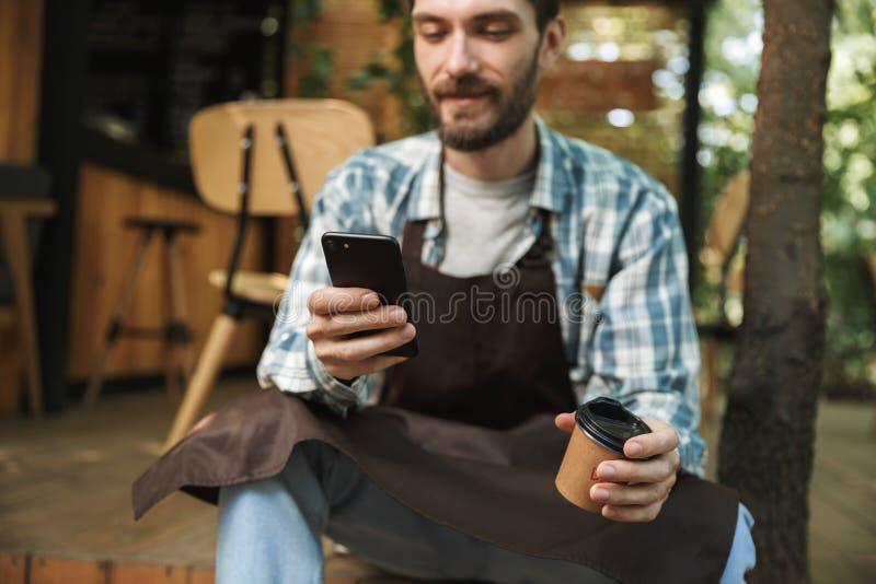 Fotografia radosny kelnera mężczyzna używa smartphone w kawiarni lub coffeehouse plenerowych podczas gdy pracujący fotografia stock