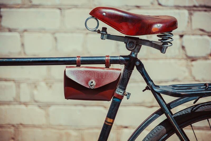 Fotografia rocznika stary rower który stoi blisko ściana z cegieł, Zamyka up stara, będąca ubranym bicykl rama, w której skóra, zdjęcia royalty free