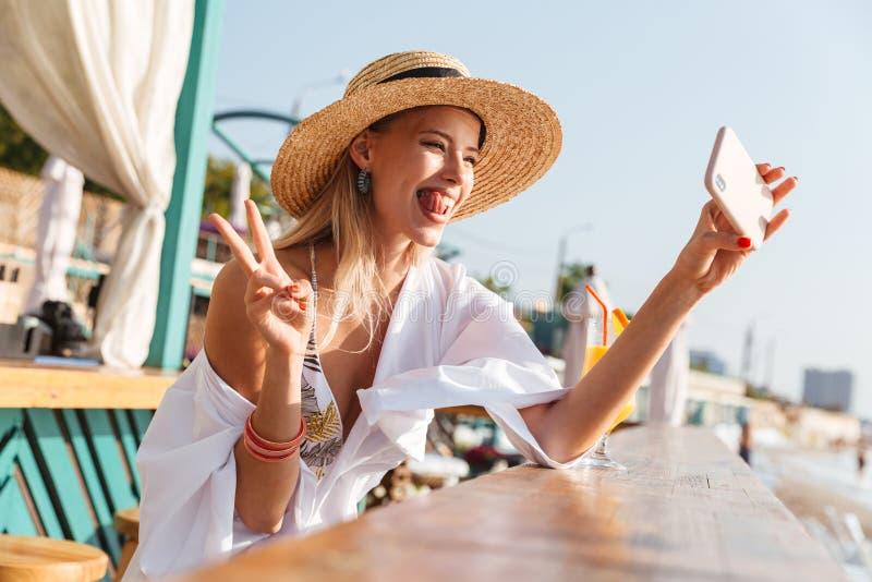 Fotografia rozochocona blondynki kobieta 20s w słomiany kapeluszu śmiać się, Tak i fotografia stock