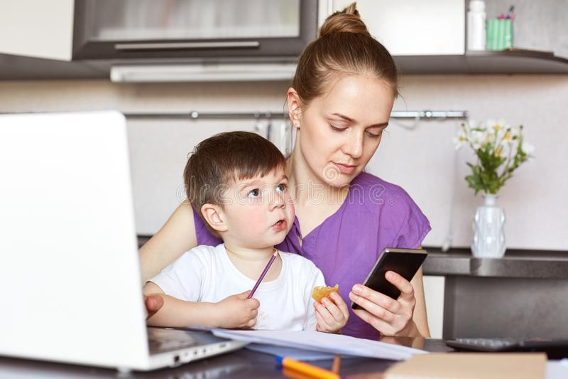 Fotografia ruchliwie pracujących matek próby rozwiązywać pieniężnych problemy, czekania dla wezwania, chwyta mądrze telefon, sied obraz royalty free