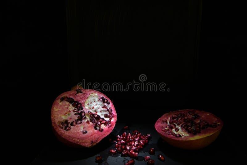 Fotografia scura di natura morta con la frutta rossa del melograno fotografie stock libere da diritti
