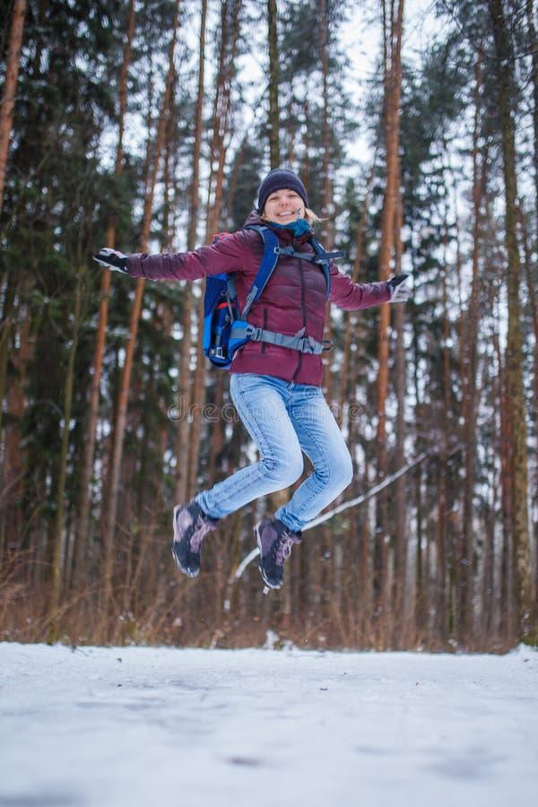 Fotografia skokowa kobieta z plecaka odprowadzeniem w zima lesie zdjęcia stock
