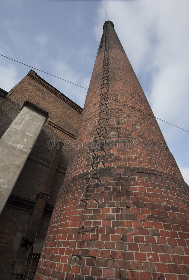 Fotografia stary ceglany fabryczny komin z żelaznym wspornika schodkiem kroczy patrzeć lata błękitny chmurny niebo zdjęcie stock