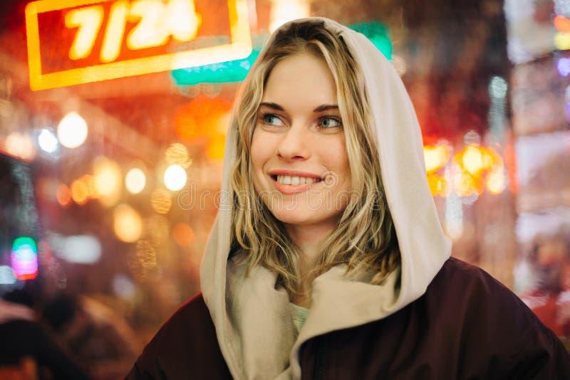 Fotografia szczęśliwa blondynka na zamazanym tle miasto zaświeca obraz royalty free