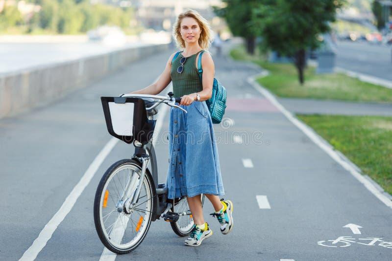 Fotografia szczęśliwa blondynka w długiej drelich spódnicy pozycji obok roweru na drodze w mieście zdjęcie royalty free