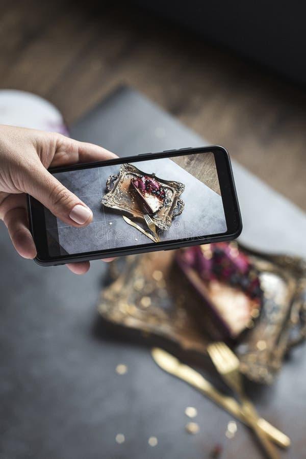 Fotografia tort i tableware na telefonie żeńska ręka z pięknym manicure'em Szary tło zdjęcie stock