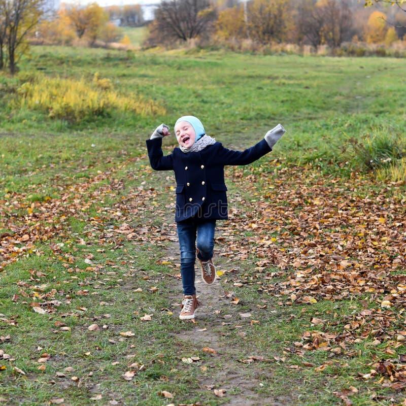 Fotografia uśmiechnięty mała dziewczynka bieg na ścieżce w jesień parku zdjęcia stock