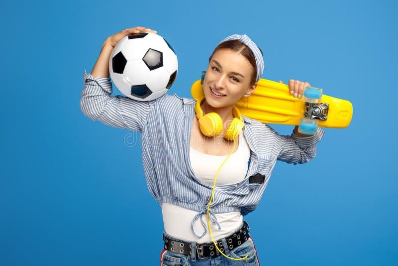 Fotografia urocza młoda kobieta z, piłki nożnej piłka i hełmofony pozuje nad błękitnym tłem żółtym centem lub deskorolka, zdjęcia stock