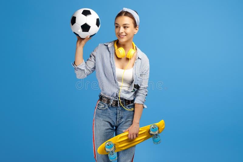 Fotografia urocza młoda kobieta z, piłki nożnej piłka i hełmofony pozuje nad błękitnym tłem żółtym centem lub deskorolka, fotografia stock